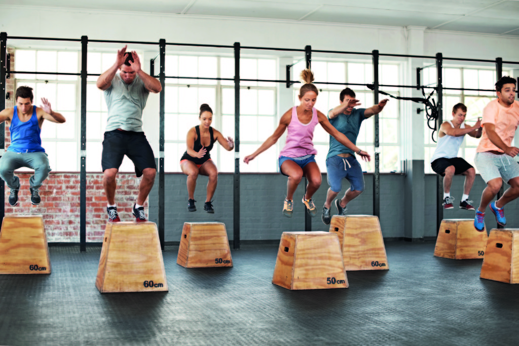 Shot of a group of people jumping onto boxes in a crossfit class