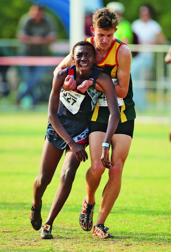POTCHEFSTROOM, SOUTH AFRICA - Saturday 9 September 2017, Ronen Oosthuizen of Athletics North West helps Mpho Mitchell of of Athletics Gauteng North to the finish line in the Boys U16 6km race during the South African Cross Country Championships at the North West University Joolplaas in Potchefstroom. Photo by Roger Sedres/ ImageSA